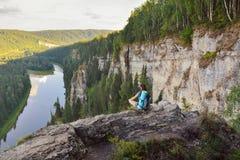 Mujer joven con la mochila que se sienta en el cliff& x27; borde de s en la alta montaña Imágenes de archivo libres de regalías
