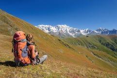 Mujer joven con la mochila que se sienta en el top que mira a la montaña Fotos de archivo libres de regalías