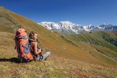 Mujer joven con la mochila que se sienta en el top y que mira a la montaña Foto de archivo