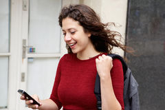 Mujer joven con la mochila usando el teléfono móvil Foto de archivo libre de regalías