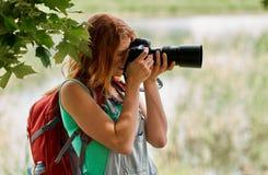 Mujer joven con la mochila y la cámara al aire libre Imagen de archivo