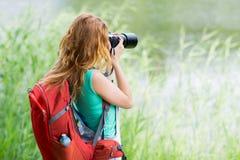 Mujer joven con la mochila y la cámara al aire libre Imágenes de archivo libres de regalías