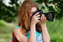 Mujer joven con la mochila y la cámara al aire libre Fotografía de archivo libre de regalías