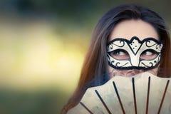 Mujer joven con la máscara y fan Fotos de archivo libres de regalías