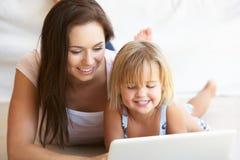 Mujer joven con la muchacha que usa el ordenador portátil Imagen de archivo