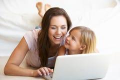 Mujer joven con la muchacha que usa el ordenador portátil Imagenes de archivo