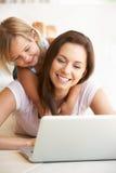 Mujer joven con la muchacha que usa el ordenador portátil Foto de archivo libre de regalías