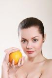 Mujer joven con la naranja aislada en blanco Imagenes de archivo