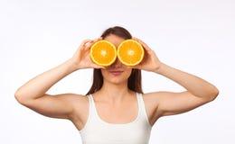 Mujer joven con la naranja partida en dos Imágenes de archivo libres de regalías