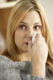 Mujer joven con la nariz que sopla fría Fotos de archivo