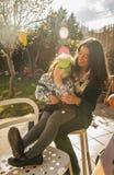 Mujer joven con la niña que juega en el patio trasero Raylight i Imágenes de archivo libres de regalías