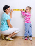 Mujer joven con la niña y el nivel de la medida Imagenes de archivo