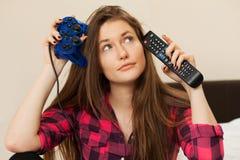 Mujer joven con la palanca de mando y la consola de la TV Imagenes de archivo