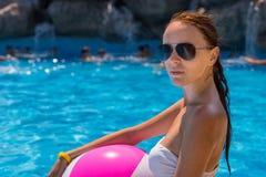 Mujer joven con la pelota de playa por la piscina Imagen de archivo libre de regalías