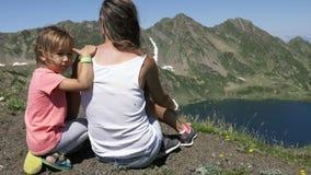 Mujer joven con la pequeña hija linda que se sienta encima de la montaña almacen de metraje de vídeo