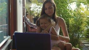 Mujer joven con la pequeña hija linda que usa el ordenador portátil junto en la cámara lenta almacen de metraje de vídeo