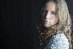 Mujer joven con la piel justa, los ojos azules y el pelo rizado marrón claro en la iluminación dramática Fotografía de archivo libre de regalías