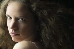 Mujer joven con la piel justa, los ojos azules y el pelo rizado marrón claro en la iluminación dramática Fotos de archivo