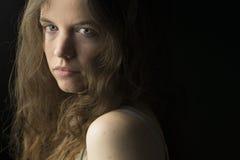 Mujer joven con la piel justa, los ojos azules y el pelo rizado marrón claro en la iluminación dramática Foto de archivo