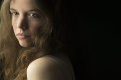 Mujer joven con la piel justa, los ojos azules y el pelo rizado marrón claro en la iluminación dramática Fotografía de archivo