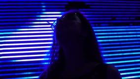 Mujer joven con la piruleta en el fondo de la cartelera del anuncio, ciudad de la noche metrajes