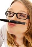 Mujer joven con la pluma en boca Fotos de archivo libres de regalías