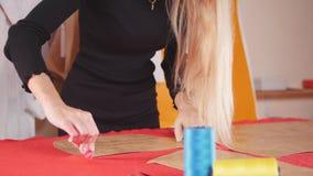 Mujer joven con la prótesis del brazo en la fábrica de costura que hace bosquejos en el paño Hilo de coser en foco almacen de video