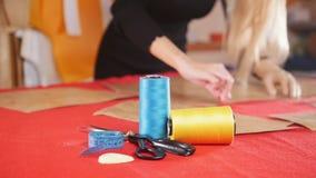 Mujer joven con la prótesis del brazo en la fábrica de costura que hace bosquejos en el paño rojo Hilo de coser en foco almacen de video