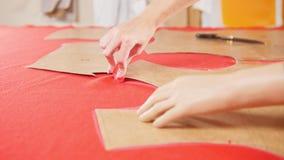Mujer joven con la prótesis del brazo en la fábrica de costura que hace bosquejos en el paño rojo Manos en foco almacen de metraje de vídeo