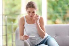 Mujer joven con la prueba de embarazo en casa fotos de archivo libres de regalías