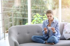 Mujer joven con la prueba de embarazo en casa imagen de archivo