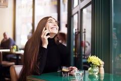 Mujer joven con la risa y la sonrisa largas, café de consumición del pelo que tiene resto en café cerca de ventana Foto de archivo