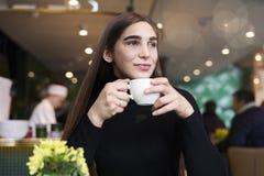 Mujer joven con la sensación larga del pelo sola, soñando, café de consumición en las manos que tienen resto en café cerca de ven Fotografía de archivo libre de regalías