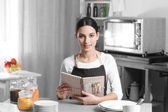 Mujer joven con la sentada del libro de cocina fotos de archivo libres de regalías