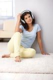 Mujer joven con la sonrisa de los auriculares Imágenes de archivo libres de regalías