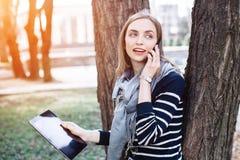 Mujer joven con la tableta digital a disposición que habla en el teléfono móvil con el novio antes de una reunión con ella Muchac Foto de archivo libre de regalías