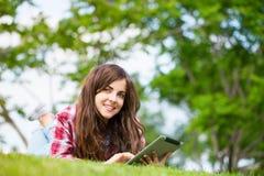 Mujer joven con la tableta digital en la hierba Imagen de archivo