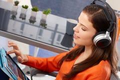 Mujer joven con la tableta y los auriculares Imágenes de archivo libres de regalías