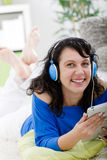 Mujer joven con la tableta y los auriculares en casa Imagen de archivo