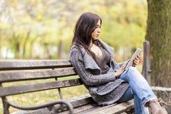 Mujer joven con la tablilla en el banco Imagen de archivo