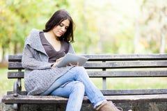 Mujer joven con la tablilla en el banco Imagenes de archivo