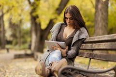 Mujer joven con la tablilla en el banco Fotografía de archivo