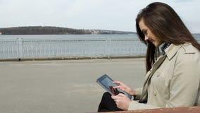 Mujer joven con la tablilla en el banco metrajes