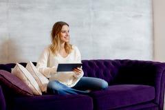 Mujer joven con la tablilla en el sofá imagenes de archivo
