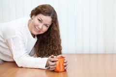 Mujer joven con la taza anaranjada en las manos que miran la cámara Fotografía de archivo