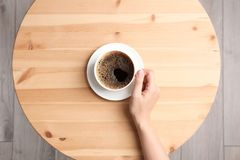 Mujer joven con la taza de café delicioso en la tabla, visión superior fotografía de archivo