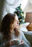 Mujer joven con la taza de café a disposición que se sienta cerca de la ventana Foto de archivo libre de regalías