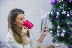 Mujer joven con la taza de chocolate caliente delante del árbol de navidad foto de archivo