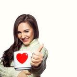 Mujer joven con la taza de té que sonríe en cámara Imágenes de archivo libres de regalías