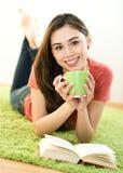 Mujer joven con la taza y el libro Foto de archivo